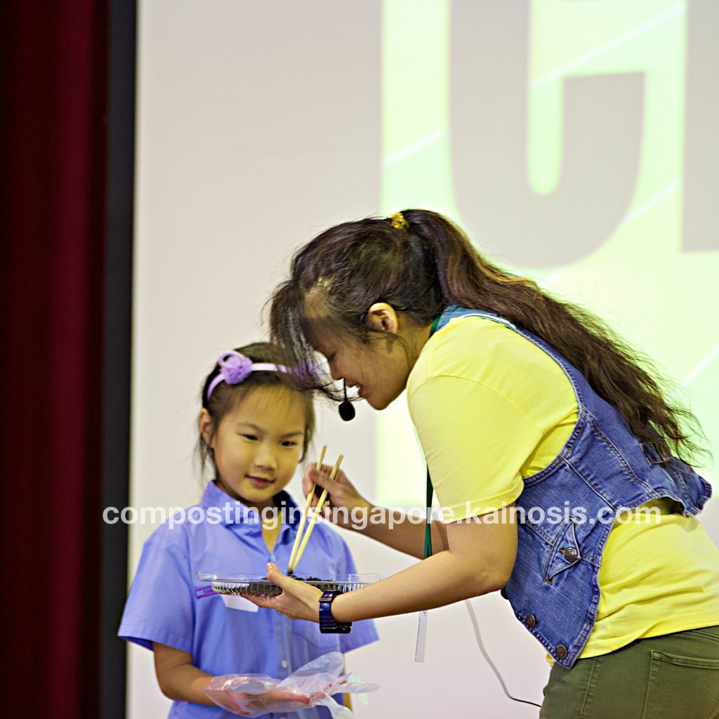 Girl volunteers to come up onstage to interact with composting worms and answer a quiz question