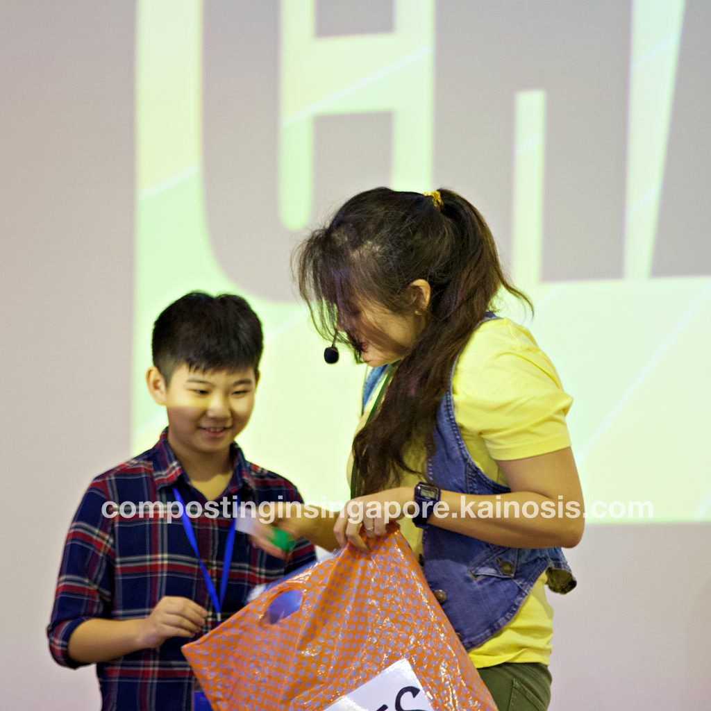 Boy comes up onstage to answer a quiz question - and wins a prize from the bag!