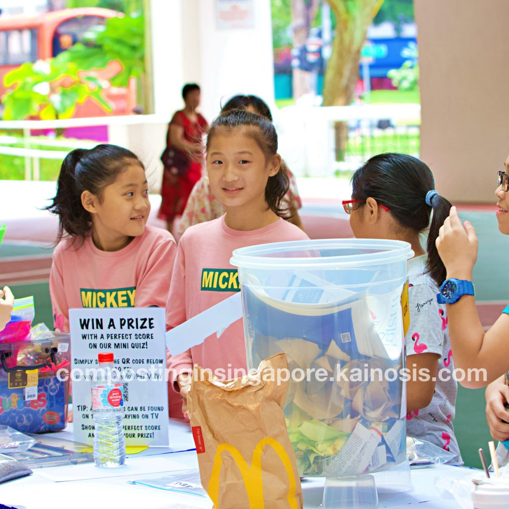 Children participating in a compost quiz trivia at the prizes and freebies station