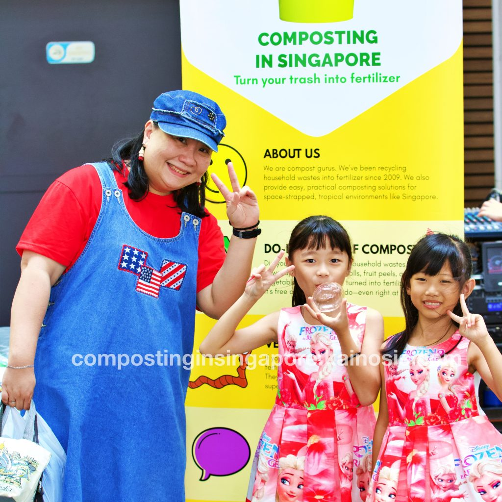 A family rocking a great look in front of our composting banner!