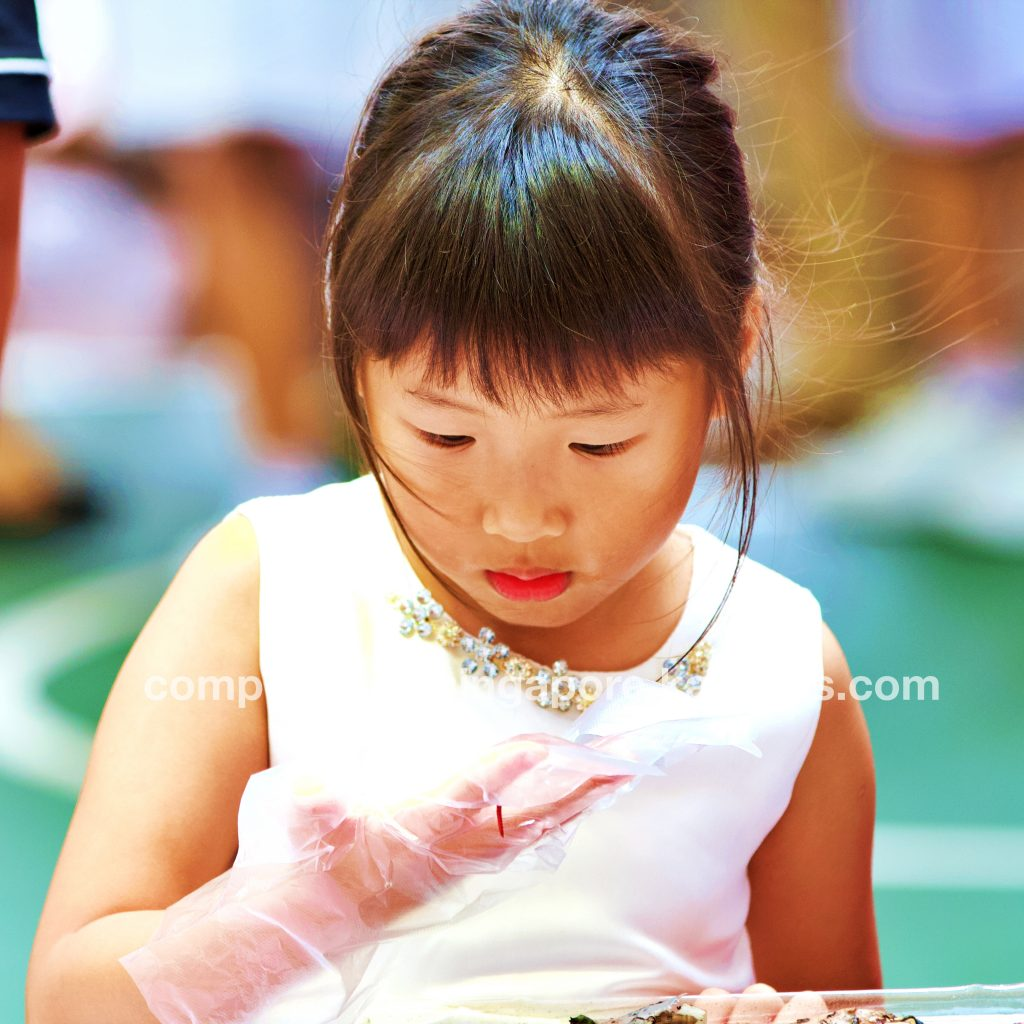 Brave little girl holds a composting worm in her hand and looks at it upclose