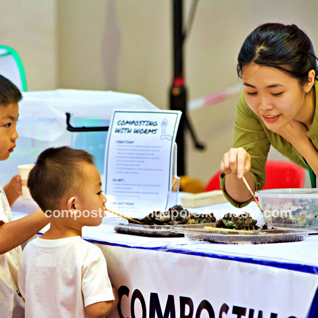 Booth facilitator welcoming the children to interact with composting worms