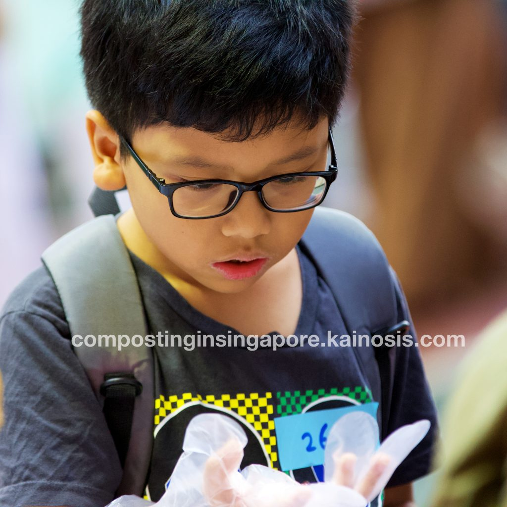 Boy observing a composting worm in his hand while a family member takes a snapshot