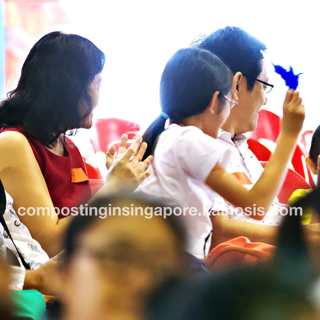 A family applauding after receiving prizes during a compost quiz